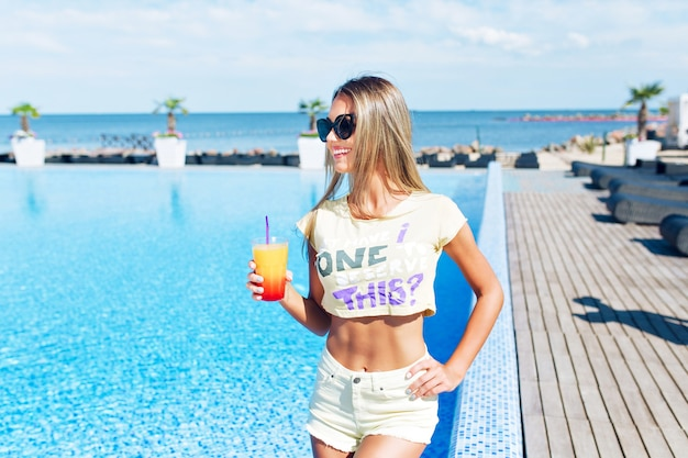 Jolie fille blonde aux cheveux longs se tient près de la piscine. . elle tient un cocktail et sourit.