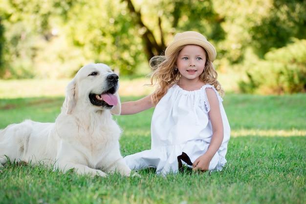 Une jolie fille blonde aux yeux bleus et un gros chien blanc dans un parc ensoleillé d'été.