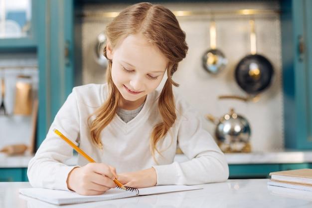 Jolie fille blonde de contenu souriant et écrivant dans son cahier alors qu'il était assis à la table