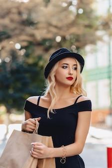 Jolie fille blonde dans un chapeau après le shopping dans les rayons du soleil de l'été