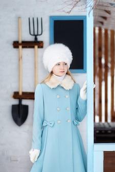 Jolie fille blonde dans un manteau bleu et un chapeau de fourrure blanche en hiver. temps neigeux. la jeune fille sur le porche de la maison. maison d'hiver. modèle posant dans la rue. le concept de vacances d'hiver.