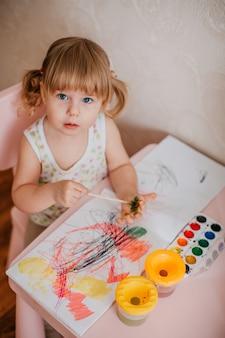 Jolie fille blonde avec deux ponytales en train de dessiner à l'aquarelle sur une main, assise à une table rose