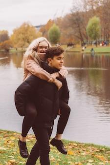 Une jolie fille blonde est assise sur le dos d'un charmant homme brune. les adolescents aimants sont heureux, souriants