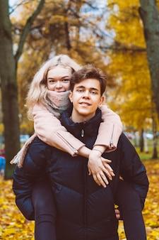 Une jolie fille blonde est assise sur le dos avec un charmant homme brune. les adolescents aimants sont heureux,