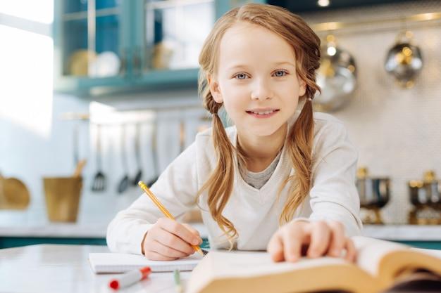 Jolie fille blonde exubérante souriant et écrivant dans son cahier alors qu'il était assis à la table avec un livre