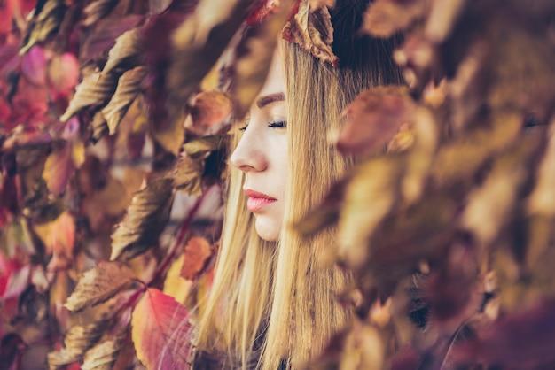 Jolie fille blonde avec des feuilles d'automne