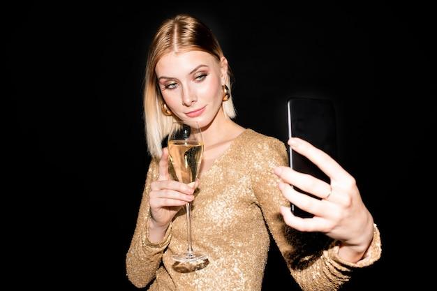 Jolie fille blonde avec flûte de champagne et smartphone faisant selfie tout en tenant un verre par sa poitrine et en regardant la caméra