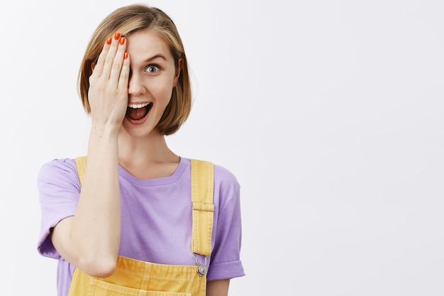 Jolie fille blonde jouant peekaboo, montrant la moitié du visage et souriant amusé