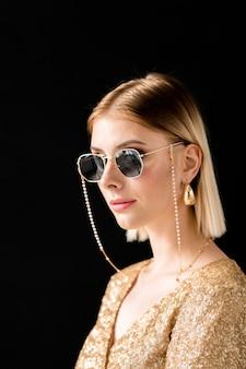Jolie fille blonde en lunettes de soleil glamour, robe élégante et boucles d'oreilles dorées debout devant la caméra sur fond noir