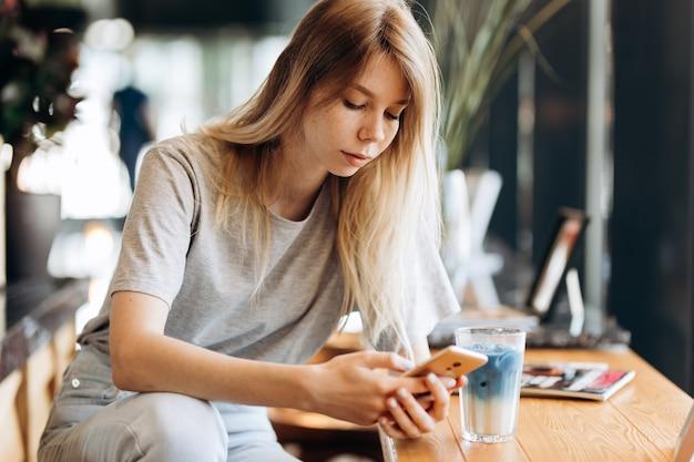 Une jolie fille blonde mince, vêtue d'un style décontracté, boit du café et regarde son téléphone dans un café. .