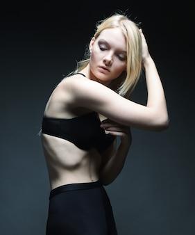 Jolie fille blonde en noir sur mur gris