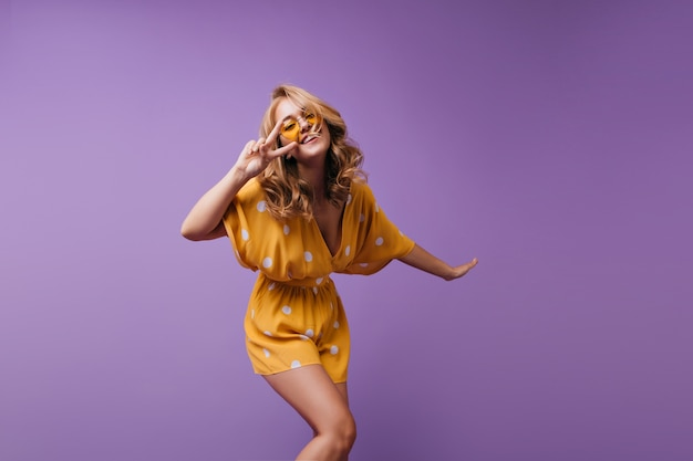 Jolie fille blonde avec une peau bronzée dansant et riant. portrait de joyeuse dame européenne exprimant des émotions positives.