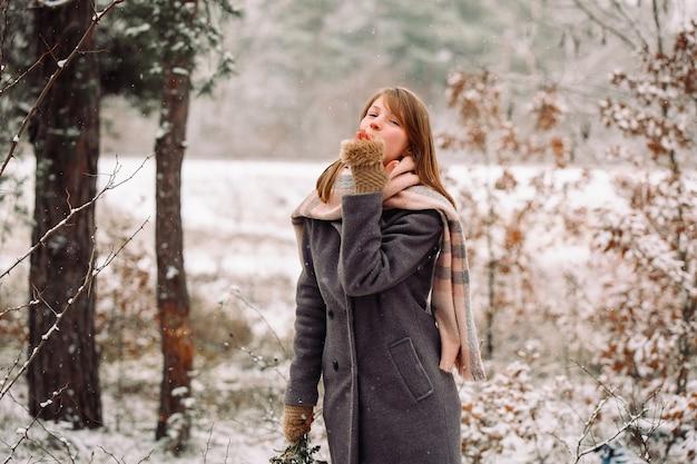 Une jolie fille blonde portant un manteau gris ultime avec une écharpe chaude et des gants envoie un baiser d'air à