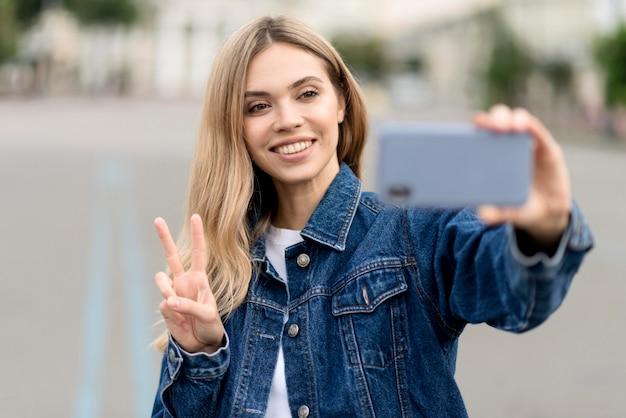 Jolie fille blonde prenant un signe de paix selfie