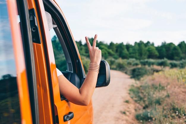 Jolie fille blonde qui décolle du bras dans la fenêtre de la voiture avec v sur les doigts