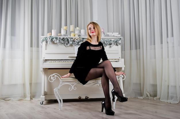 Jolie fille blonde en robe noire contre le piano du nouvel an avec des bougies de noël.