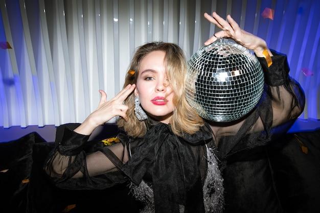 Jolie fille blonde en robe de soirée en organza noir tenant une boule disco scintillante par sa tête tout en profitant de la fête en boîte de nuit
