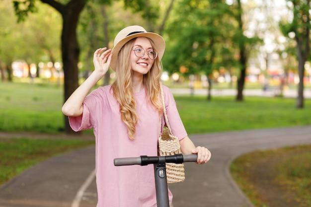 Jolie fille blonde avec un scooter électronique dans le parc en été