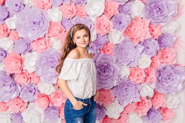 Jolie fille blonde se tient et tient les mains dans ses poches en souriant. elle a un fond rose couvert de fleurs