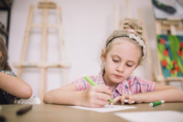 Jolie fille blonde de sept ans, dessine à table dans le studio de création.