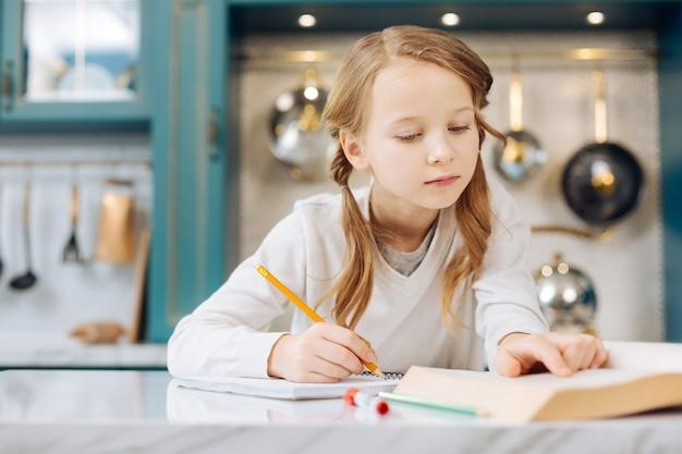 Jolie fille blonde souriante et écrivant dans son cahier alors qu'il était assis à la table et lisant un livre