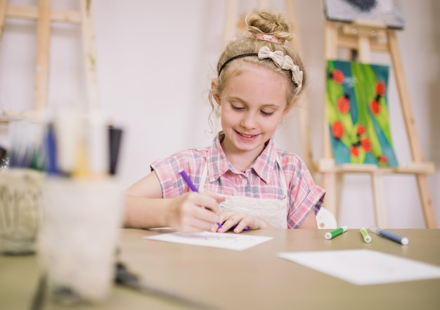 Jolie fille blonde souriante de sept ans, dessine à table dans le studio de création.