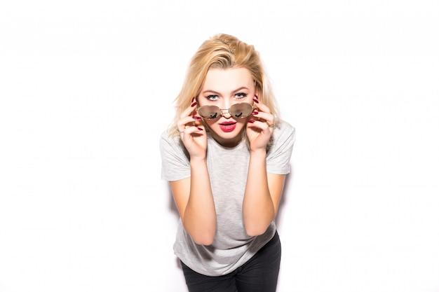 Jolie fille blonde tient des lunettes de soleil brillantes sur son visage
