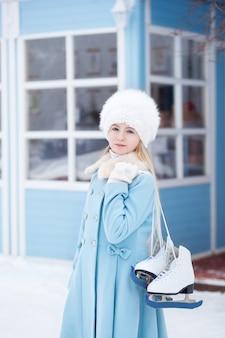 Une jolie fille blonde va patiner à l'extérieur. une fille dans un manteau bleu et un chapeau de fourrure avec des patins à la maison d'hiver. activités le week-end par temps froid. noël, concept de vacances d'hiver. sport d'hiver.