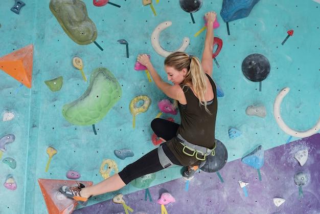 Jolie fille blonde en vêtements de sport et ceinture de sécurité sur les hanches en gardant les pieds sur des rochers multicolores et en les saisissant pendant la pratique de l'escalade dans la salle de sport.