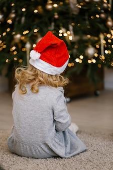 Jolie fille en bonnet de noel est assise sous un arbre de noël festif. les fêtes de noel