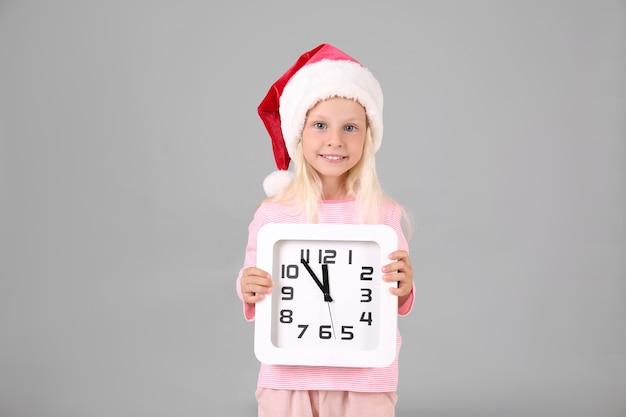 Jolie fille en bonnet de noel avec horloge sur surface grise