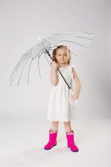 Jolie fille en bottes de caoutchouc sous parapluie transparent