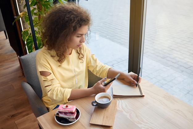 Jolie fille bouclée écrit des notes, buvant du café en café.