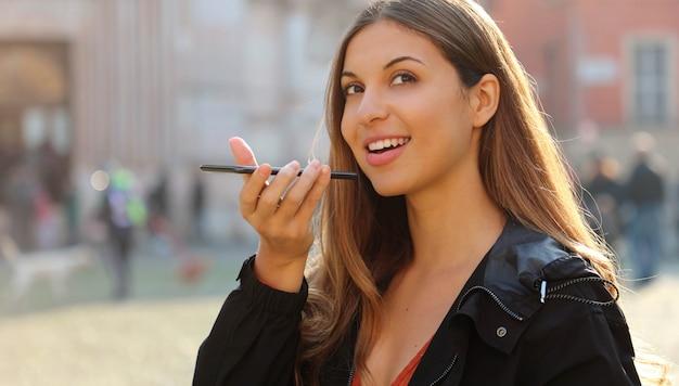 Jolie fille brésilienne tenant le téléphone parle avec assistant vocal numérique virtuel sur smartphone dans la rue de la ville.