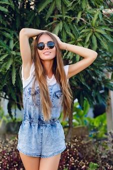 Jolie fille bronzée mince debout près de l'arbre. elle porte un t-shirt blanc, un short en jean et des lunettes de soleil noires