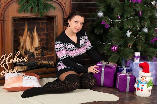 Jolie fille brune à l'arbre de noël avec des cadeaux