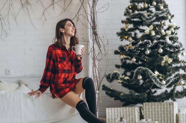 Jolie fille brune au lit portant une chemise rouge et des chaussettes chaudes avec une tasse de café et des lumières de noël derrière