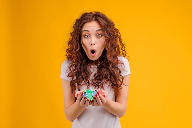 Jolie fille brune aux cheveux bouclés isolé pariant dans le casino en ligne. concept de poker en ligne.