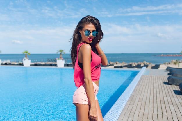 Jolie fille brune aux cheveux longs pose à la caméra près de la piscine. elle regarde en bas.