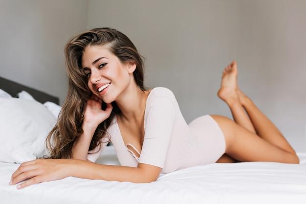 Jolie fille brune aux cheveux longs en pyjama portant sur le lit. elle a un sourire blanc comme neige, regardant.
