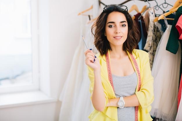 Une jolie fille brune dans une robe grise et une veste jaune est debout près de vêtements en atelier. elle tient un crayon dans une main et sourit à la caméra.