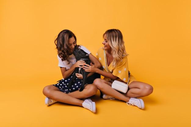 Jolie fille brune embrassant le bouledogue français. portrait intérieur de deux meilleurs amis posant avec mignon chiot noir.