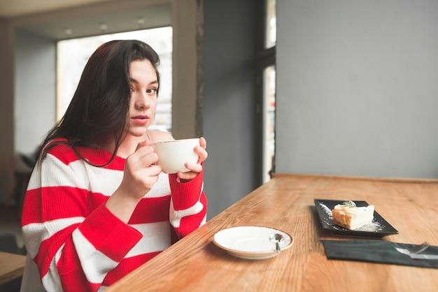 Jolie fille brune est assise dans un café avec une tasse de café