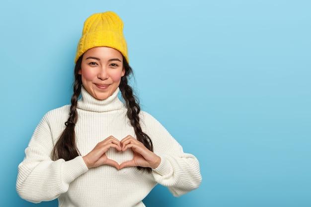 Jolie fille brune fait signe de la main du cœur, sourit agréablement, porte un chapeau jaune et un pull blanc, exprime l'amour et l'affection, a une expression satisfaite, des modèles sur fond bleu, copie espace