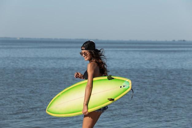 Jolie fille brune mince dans des lunettes de soleil et une casquette sourit et tient une planche de surf jaune près de la mer par une journée ensoleillée. .