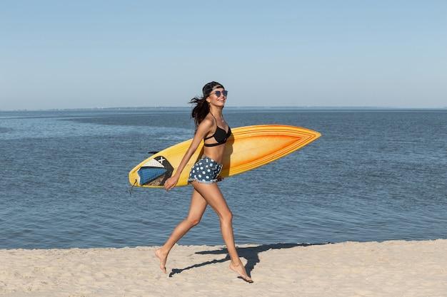 Jolie fille brune mince en lunettes de soleil et casquette vêtue d'un soutien-gorge noir et d'un jean court près de la mer et tient une planche de surf jaune par une journée ensoleillée. .