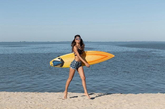 Jolie fille brune mince en lunettes de soleil et casquette vêtue d'un soutien-gorge noir et d'un short en jean s'amuse près de la mer et tient une planche de surf jaune par une journée ensoleillée. .