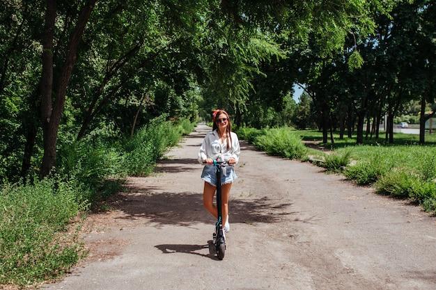 Jolie fille brune monte sur un scooter à électrodes dans le parc, elle porte une chemise blanche. concept de transport écologique et de location.