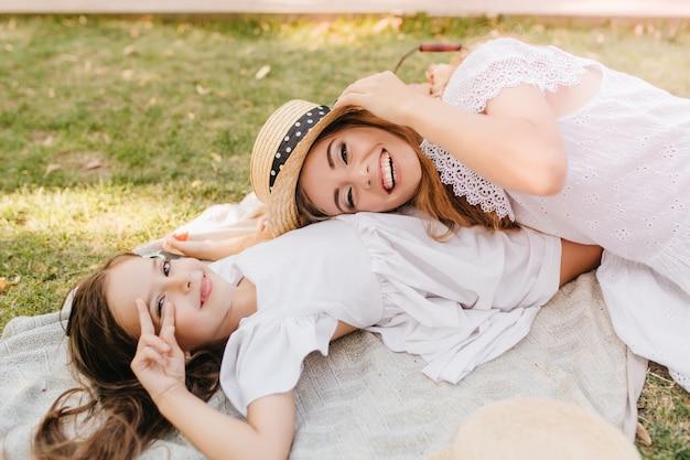 Jolie fille brune posant avec signe de paix sur l'herbe tandis que sa charmante mère tenant un chapeau de paille et riant. jolie jeune femme en tenue de dentelle s'amuser avec sa fille sur une couverture dans le parc.