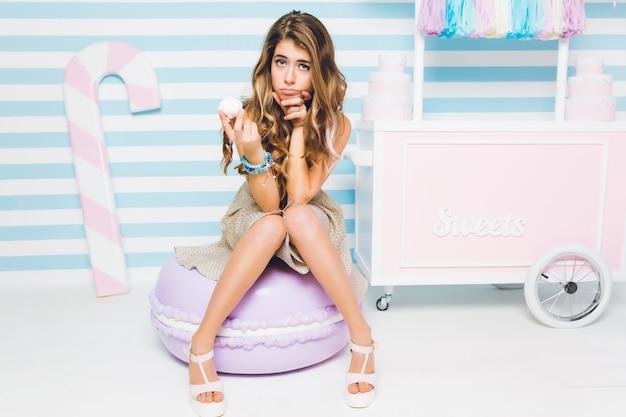 Jolie fille brune sur un régime réfléchit à l'opportunité de manger de la guimauve assis sur un mur rayé. portrait de jeune femme séduisante avec un gâteau savoureux à la main sur le gros macaron jouet.